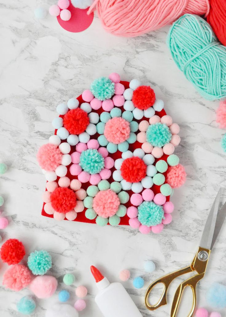 Inspired by floral swim caps from the '60s, this DIY pom-pom- covered winter hat...