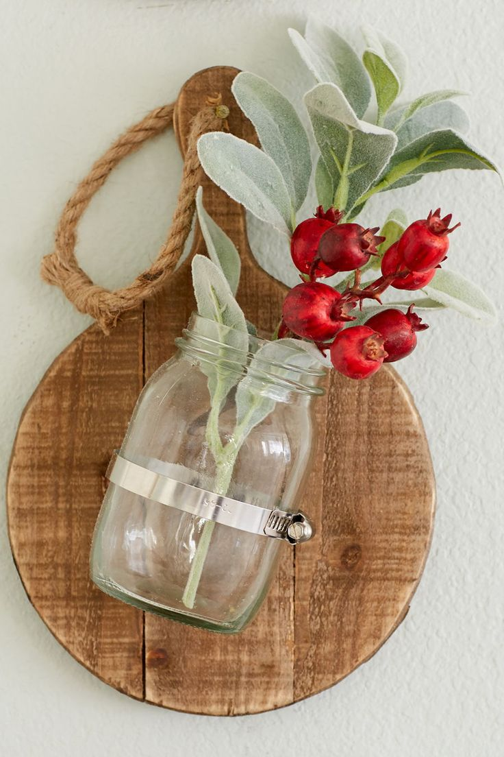 Breadboards with mason jars attached are a festive way to display holiday floral...